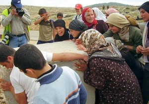 Women and children of At-Tuwani  in the South Hebron Hills, Palestine remove roadblock to their village